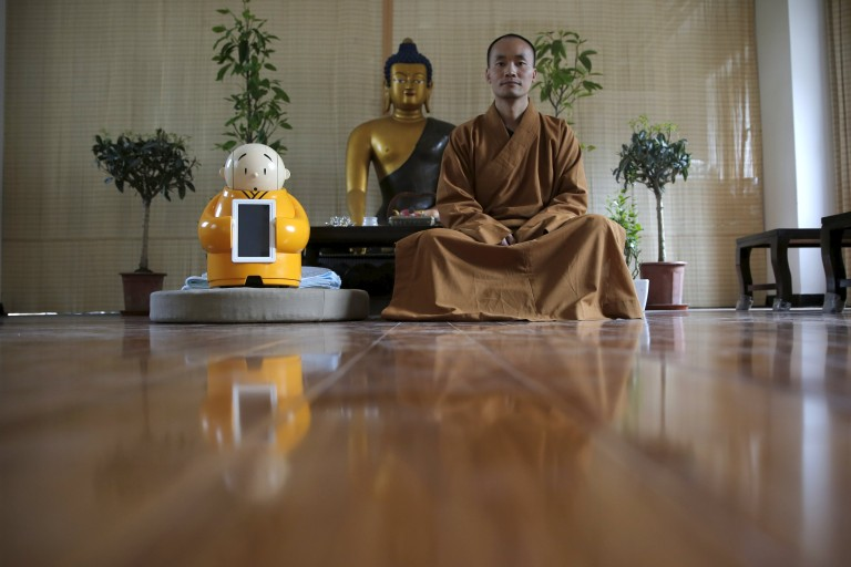 Master Xianfan sits next to robot Xian'er as he poses for photograph at Longquan Buddhist temple on the outskirts of Beijing, April 20, 2016.  REUTERS/Kim Kyung-Hoon