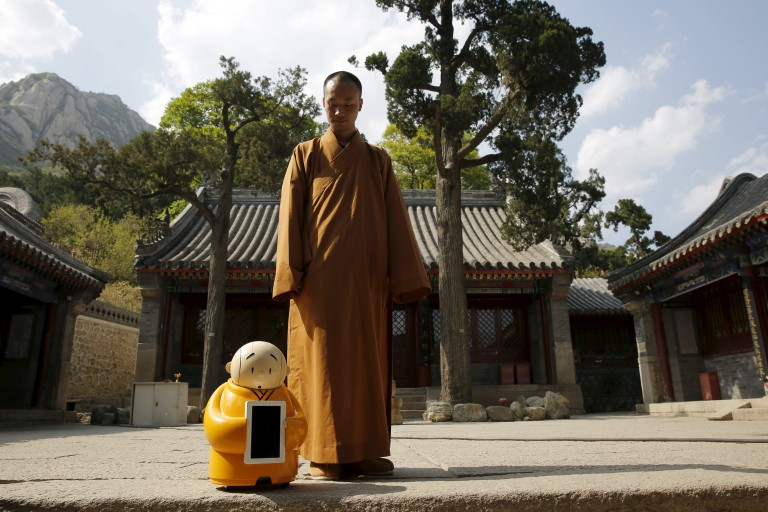 Master Xianfan looks at robot monk Xian'er as he prepares to pose for photograph in the main building of Longquan Buddhist temple on the outskirts of Beijing, April 20, 2016.  REUTERS/Kim Kyung-Hoon