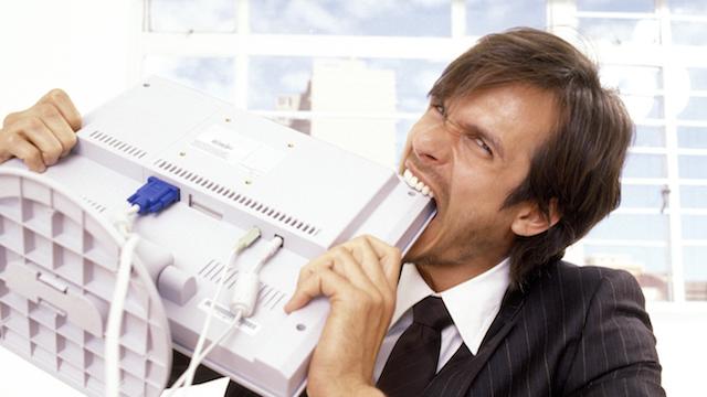 Businessman biting a computer monitor