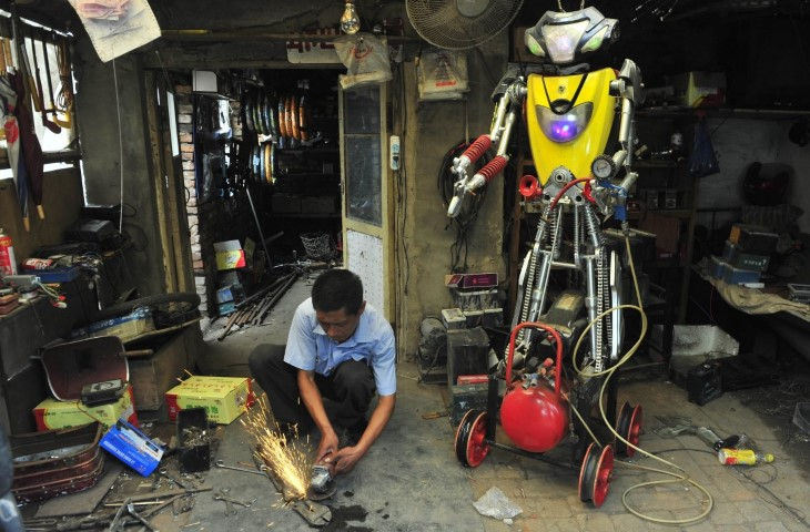 a-49-year-old-electric-bike-mechanic-who-identified-himself-only-as-wu-welds-a-component-to-fit-onto-his-newly-made-robot-at-his-repair-shop-in-shenyang-liaoning-province-june-25-2012