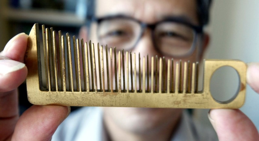 han-yuzi-63-inventor-holds-up-one-of-his-creations-a-hair-comb-that-doubles-as-a-small-hand-held-musical-instrument-in-guangzhou-the-capital-of-chinas-guangdong-province-september-13-2003