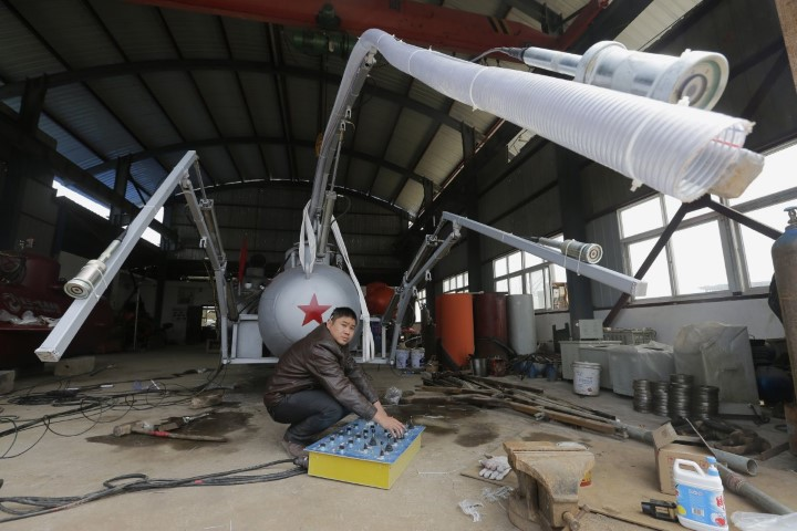 zhang-wuyi-looks-up-as-he-squats-under-a-suction-pipe-of-his-submarine-that-captures-sea-cucumbers-at-his-workshop-in-wuhan-hubei-province-march-25-2013