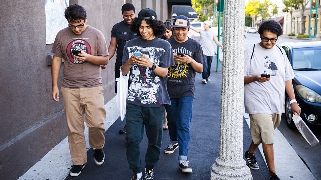Fullerton, United States - July 13, 2016: Image of people playing pokemon go game on an iphone smartphone devices. Pokemon Go is a popular virtual reality game for mobile devices.
