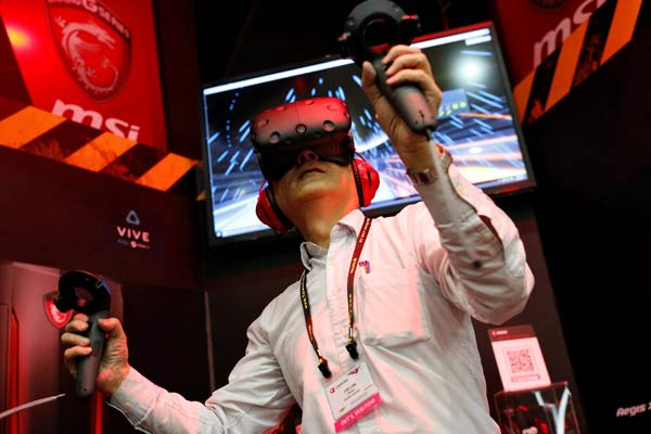 A visitor tries a pair of HTC Vive virtual reality (VR) goggles, during the annual Computex computer exhibition in Taipei, Taiwan